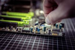 El experto está poniendo el puente eléctrico en contactos de la placa madre con los fórceps miniatura negros fotos de archivo