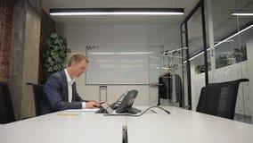 El experto experimentado trabaja en la tabla con PC y escribe, sentándose en compañía almacen de video