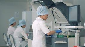 El experto femenino del laboratorio está poniendo muestras en analizador de la química clínica almacen de video