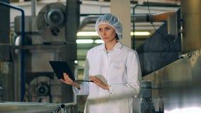 El experto femenino está trabajando en un ordenador portátil en la instalación de la fábrica almacen de metraje de vídeo