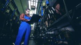 El experto masculino está actuando un ordenador portátil en una unidad de ordeño de las vacas metrajes