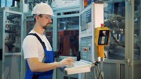 El experto masculino está actuando un panel de control en premisas de fábrica almacen de metraje de vídeo