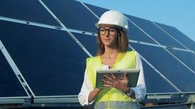 El experto sonriente de la señora se está colocando cerca de una batería solar con una tableta almacen de video