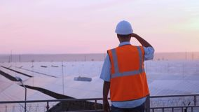El experto técnico en los paneles fotovoltaicos de energía solar, teledirigidos realiza las acciones rutinarias para la supervisi almacen de video