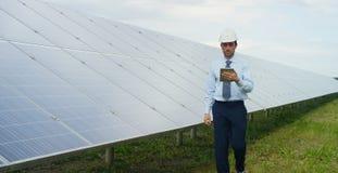 El experto técnico en los paneles fotovoltaicos de energía solar, teledirigidos realiza las acciones rutinarias para la supervisi Imagenes de archivo