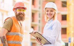 El experto y el constructor comunican sobre los materiales de construcción de la fuente Concepto acertado del trato Compra de los imagen de archivo