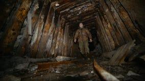 El explorador con una linterna camina a lo largo de una mina abandonada vieja con los carriles metrajes