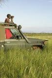 El explorador del Masai con los prismáticos busca animales de un Landcruiser durante una impulsión turística del juego en la cons Fotos de archivo