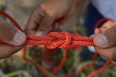 El explorador está atando el nudo de filón y x28; Cuadrado Knot& x29; foto de archivo libre de regalías