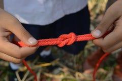 El explorador está atando el nudo de filón y x28; Cuadrado Knot& x29; fotografía de archivo libre de regalías