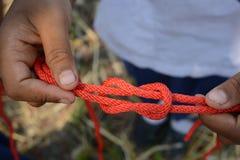 El explorador está atando el nudo de filón y x28; Cuadrado Knot& x29; foto de archivo