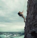 El explorador sube una montaña con el riesgo para caerse en el mar con los tiburones imagen de archivo