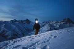 El explorador valiente con el faro confía una subida de la noche a una montaña nevosa escarpada Desgaste y mochila del esquí que  Imagen de archivo