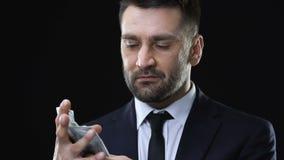 El exprimir del hombre de negocios y billetes de banco del dólar que lanzan, rechazando valor del dinero almacen de video