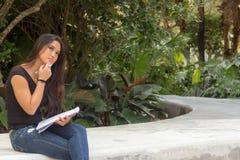 El exterior que se sienta del estudiante asiático femenino piensa mientras que escribe adentro no Fotos de archivo libres de regalías