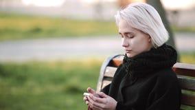 El exterior rubio de la muchacha mira el smartphone en juegos de un banco que sonríe un juego activo 3D en smartphone almacen de video
