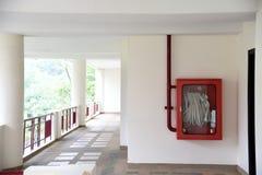 El extintor y la manguera de bomberos aspan en pasillo del hotel Estante de las mangueras de bomberos para el uso fotografía de archivo libre de regalías
