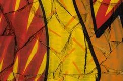 El extracto coloreó textura bajo la forma de pintura anaranjada y amarilla roja pintada en la pared de tejas quebradas Foto de archivo