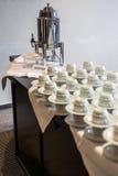 El extracto empañó muchas filas de las tazas de té del café con el dispensador del café Fotografía de archivo