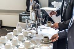 El extracto empañó muchas filas de las tazas de té del café con los hombres de negocios del dispensador del café que tomaban uno Foto de archivo libre de regalías
