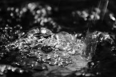 El extracto salpica del agua en un fondo negro Fotos de archivo