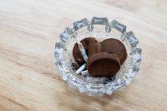 El extremo de cigarrillos en cenicero con reutilizado para la ruina del café de la rutina a utilizado hace las cenizas Fotografía de archivo