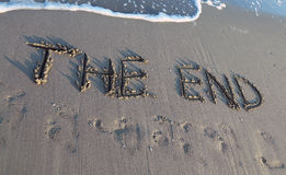 EL EXTREMO escrito en la playa mientras que viene la onda Imágenes de archivo libres de regalías