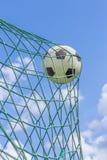 El fútbol cogió en red de la meta con el cielo azul Fotos de archivo libres de regalías