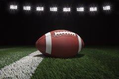 El fútbol del estilo de la universidad en campo con la raya debajo del estadio se enciende Foto de archivo libre de regalías
