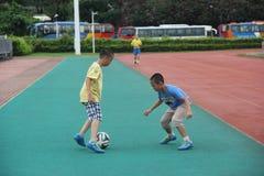 El fútbol que juega de muchachos en centro de deportes del shekou de Shenzhen Foto de archivo libre de regalías