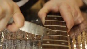 El fabricante de la guitarra muele trastes musicales en el fingerboard de la guitarra almacen de metraje de vídeo