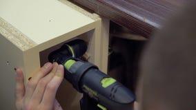 El fabricante de los muebles perfora la superficie lateral del gabinete, usando una boca de la esquina en el taladro Primer almacen de metraje de vídeo