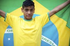 El fanático del fútbol brasileño joven orgulloso sostiene la bandera brasileña Imagenes de archivo