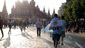 El fanático del fútbol de la Argentina del mundial del fútbol con la bandera está caminando abajo de la Plaza Roja metrajes
