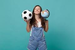 El fanático del fútbol relajado de la mujer anima para arriba el equipo preferido de la ayuda con el balón de fútbol, globo del m imagen de archivo libre de regalías
