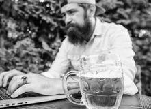 El fan apostó campeonato en línea mientras que siente la terraza al aire libre con la cerveza El inconformista barbudo del fanáti fotos de archivo libres de regalías