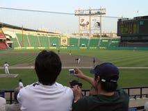 El fan fotografía el juego de béisbol con la cámara digital Imagen de archivo libre de regalías