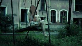El fantasma de una niña en un oscilación en la casa arruinada vieja espíritu maligno almacen de metraje de vídeo