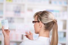 El farmacéutico de sexo femenino coge la forma de la medicina el estante Imágenes de archivo libres de regalías