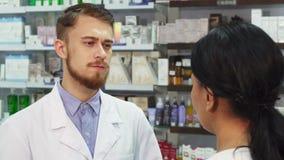 El farmacéutico escucha atento su cliente metrajes
