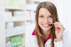 El farmacéutico sonriente charla a un paciente en auriculares Fotos de archivo libres de regalías