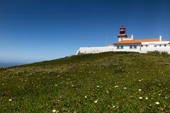El faro westernmost de Cabo DA Roca en Porugalia con el crecimiento amarillo-florecido del higo hotentote imágenes de archivo libres de regalías