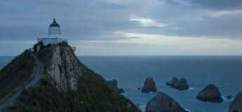 El faro y las rocas famosos en el punto de la pepita en el Catlins en la isla del sur, Nueva Zelanda después de la puesta del sol foto de archivo libre de regalías
