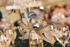 El fascinator de la mujer sobre el vidrio del champán Imágenes de archivo libres de regalías