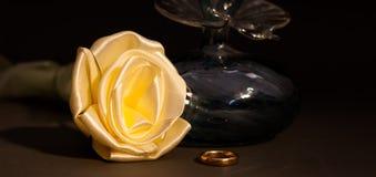 El favor y el anillo de la boda al lado de una tela subieron Imágenes de archivo libres de regalías
