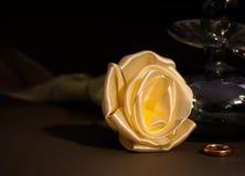 El favor y el anillo de la boda al lado de una tela subieron Imagenes de archivo