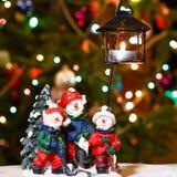 El feliz candelero de los muñecos de nieve con la vela ardiente delante del árbol de navidad se enciende Foto de archivo