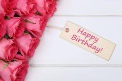 El feliz cumpleaños con las rosas florece con la tarjeta de felicitación en un de madera Imágenes de archivo libres de regalías