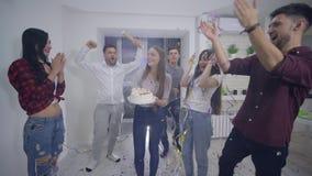 El feliz cumpleaños, el grupo de amigos divertidos de muchachos y las muchachas felicitan a la novia el día de fiesta que sopla h almacen de video