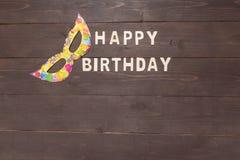 El feliz cumpleaños y la máscara están en fondo de madera Fotos de archivo libres de regalías